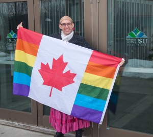 As a member of the Pride Club at TRU, Corey Keith is looking forward to a TRUSU collective with LGBTQ needs at heart. She stands in front of TRUSU proudly holding the Pride Club's flag. - Photo by Justine Cleghorn
